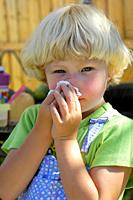 4 year old girl with allergies cleans nose with tissue.
