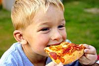 Young boy eats pizza at a picnic.