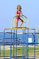 Kids play and climb on 'monkey bars' - unsafe by government standards.