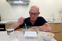 A man eats a take-out salad alone in a kitchen.