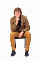 front view of middle aged man with blazer sitting on chair on white background, hand on chin,.
