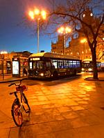 Bus stop and hire bicycle, night view. Cibeles Square, Madrid, Spain.