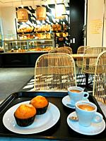 Two cups of coffee and muffins in a cafeteria.