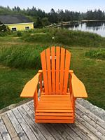 An empty adirondack chair on a deck overlooking the water, a tranquil spot, Nova Scotia, Canada.