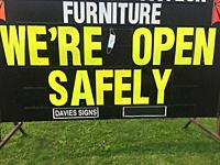 We're open safely, sign with a suggestion for wearing a mask, in a shopping area, Ontario, Canada. Many stores and businesses are responding in this w...