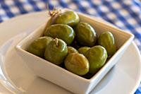 Green olives on square bowl in restaurant Andalusia Spain.