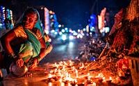 Closeup Middle-aged woman offers prayers with incense stick on the night of Diwali outdoors.