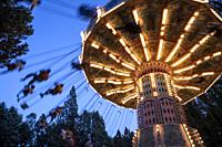 Flying chairs in the amusement park illuminated at dusk, MADRID, SPAIN, EUROPE.
