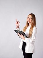 Young business woman pointing and taking notes in a folder.