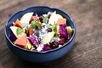 exotic mixed tropical asian fruit salad with basil seeds and coconut in bowl outdoors.