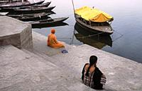 Varanasi, Uttar Pradesh, India, Asia - Two people sit at a ghat on the banks along the holy Ganges and look at the river.