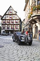 Parade of veteran cars on cobblestone street in city of Messkirch. BMW 328.