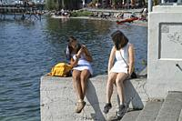 tow girls by a lake, taking photo one of the other, smartphone.