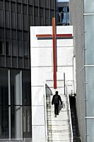 Man walking up the steps to the church in La Defense, Paris, France.