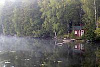 old cabin on a foggy lake shore, Imatra Finland.
