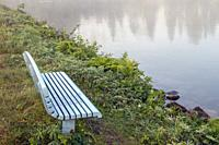 empty bench on a foggy lake shore.