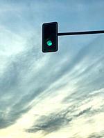 Green traffic light against nightfall sky.