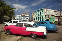 Old American cars used as taxis and colectivos in front of the colonial buildings in Center Havana, La Habana, Cuba, West Indies, Central America.
