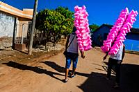 Colombian street vendors, carrying cotton candy bags for sale, walk towards the arena of Corralejas, a rural bullfighting festival held in Soplaviento...