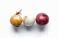 Three bulbs on a white wooden background. White onions, onions and red onions. Top view.