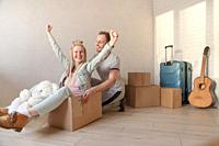 Happy young couple moving to a new apartment. A man pushes a woman sitting in a box with arms raised. Packed things in the background.