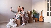 young married couple calls friends or relatives via video, moves to a new apartment or city.