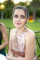 A pretty girl in an elegant light pink champagne colored dress at a wedding.