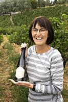 Woman, 70, with bottle of wine from a vineyard in Naramata, BC, Canada.
