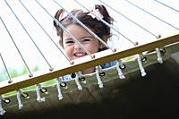 A three year old girl plays on a hammock in Tofino, British Columbia, Canada.