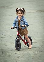 A three year old girl on her push bike on the beach at Tofino, BC, Canada.
