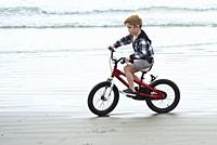 A 6 year old boy rides his bike on the beach at Tofino, BC, Canada. .
