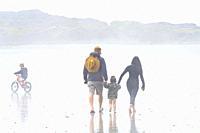 family in the fog on the beach near Tofino, British Columbia, Canada.