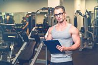 Personal trainer with is arms crossed, in a gym.