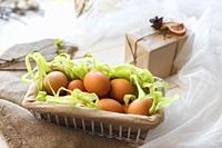 Close-up rustic basket with eggs in composition with gift box and veil.