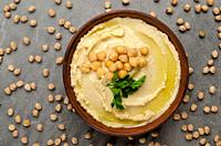 Flat lay view at hummus topped with green coriander leaves on stone table covered with chickpeas.