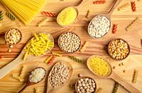 Flat lay Food background made of legumes cereals pasta and grains in wooden spoons on kitchen table.