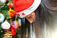 Woman decorating Christmas Tree at home.