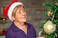 Happy elderly retired woman wearing Santa Red Hat decorating Christmas Tree at home.