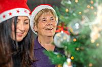 Happy elderly retired woman wearing Santa Red Hat decorating Christmas Tree at home with her daughter.