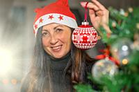 Happy Brunette Woman decorating Christmas Tree at home, holding Red Christmas Ball.