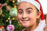 Happy smiling young girl wearing Santa Hat at home in front of Christmas Tree.