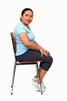 side view of a woman sitting on a chair looking at camera on white background.