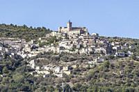 cityscape with Piccolomini castle at hilltop historical village on woody slopes, shot in bright light at Capestrano, L'Aquila, Abruzzo, Italy.