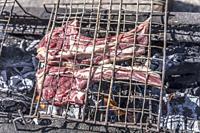 """raw mutton rib meat on grill, shot in bright light at """"""""Monti della Laga"""""""", L'Aquila, Abruzzo, Italy."""