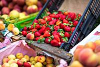 Selling fruits, strawberries, apples, peaches in a local market.