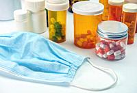 Several bottles of pills next to a mask, conceptual image.