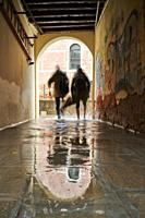 "Two adults walking trough a flooded alley in Castello Quarter. The high tide phenomenon known as """"Acqua Alta"""". Castello Quarter. Venezia. Italy."