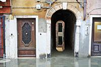 "The entrance of a residential home in Giuseppe Garibaldi Street during the high tide, locally known as """"acqua alta"""". Castello Quarter. Venezia. Ital..."