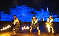 Fire artists taking part in Hogmanay Torchlight Procession perform at Edinburgh Castle prior to procession along the Royal Mile in the Old Town , Scot...