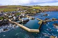 Aerial view of small fishing village and harbour of St Abbs on North Sea coast in Scottish Borders, Scotland, UK.